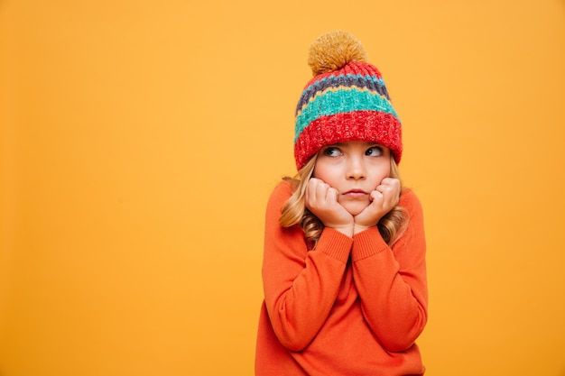 Displeased young girl in sweater and hat reclines on her arms and looking away over orange