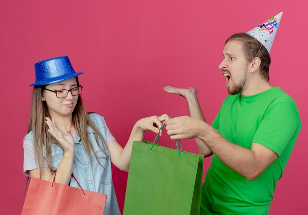 Displeased young girl wearing blue party hat holds red gift bag and raises hand taking green gift bag from annoyed young man wearing party hat isolated on pink wall