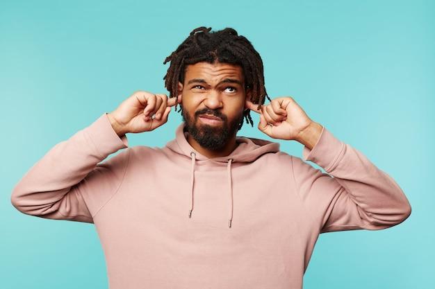 Раздосадованный молодой красивый темноволосый мужчина с бородой гримасничает и закрывает уши, пытаясь избежать громких звуков, стоя на синем фоне