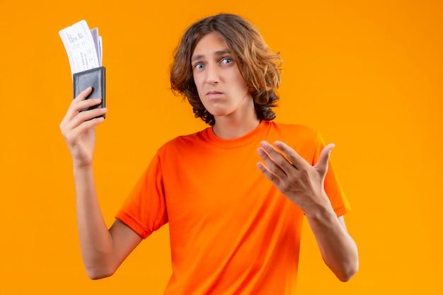 オレンジ色の背景の上に立って不幸な顔と混乱している航空券を保持しているオレンジ色のtシャツで不機嫌な若いハンサムな男