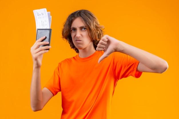 オレンジ色の背景の上に立ってダウン親指を示す航空券を保持しているオレンジ色のtシャツで不機嫌な若いハンサムな男