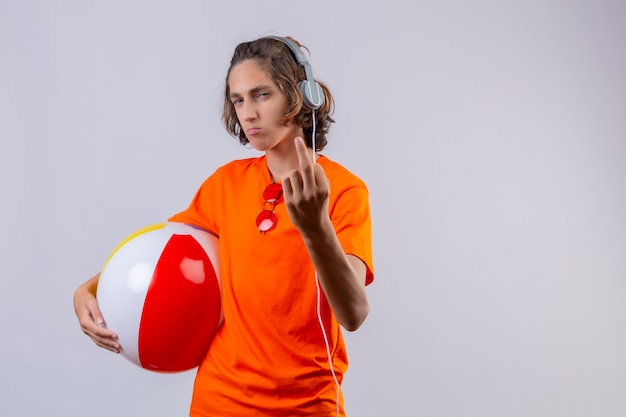 Displeased young handsome guy in orange t-shirt with headphones holding inflatable ball showing middle finger looking at camera standing
