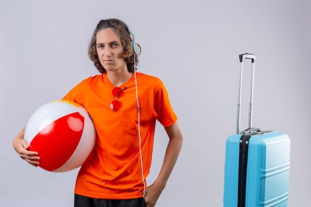 Displeased young handsome guy in orange t-shirt with headphones holding inflatable ball standing near travel suitcase