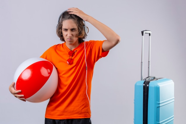 Displeased young handsome guy in orange t-shirt with headphones holding inflatable ball touching head looking a camera with frowning face standing near suitcase