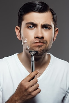 Displeased young handsome man shaving on grey