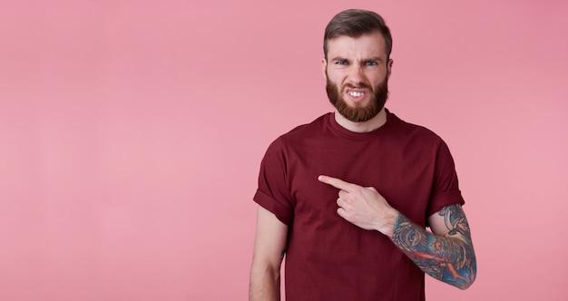 赤いシャツを着た不機嫌な若いハンサムな赤いひげを生やした男は、左側のコピースペースにあなたの注意を引きたい、顔をしかめ、嫌悪感を持ってカメラを見て、ピンクの背景の上に立っています。