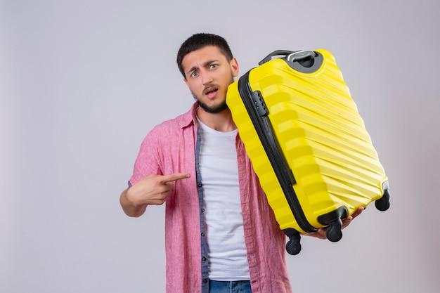 Раздосадованный молодой красивый путешественник, держащий чемодан, указывая пальцем на него, смотрит в камеру с растерянным выражением лица, стоящего на белом фоне
