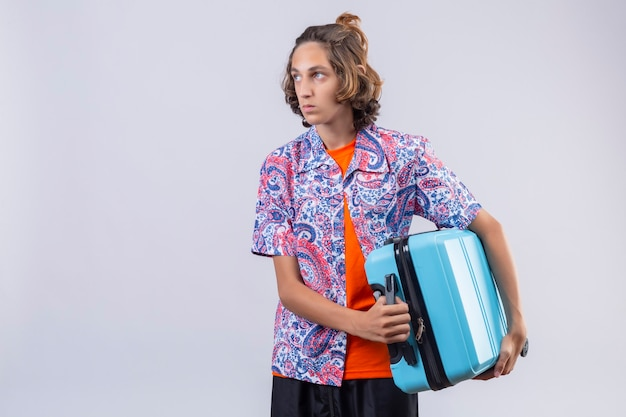 Displeased young handsome traveler guy holding suitcase on shoulder looking aside with sad expression on face standing