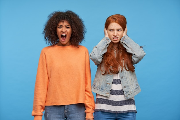 Displeased young long haired redhead woman covering her ears with raised palms while posing over blue wall with stressed brown haired dark skinned screaming female