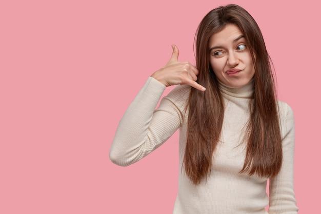 La giovane adorabile signora scontenta gesti al coperto, fa il segnale di chiamata con la mano