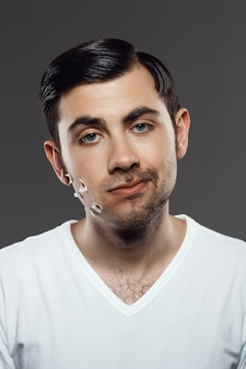 Displeased young man after shaving on grey