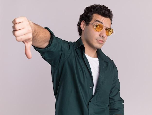 흰색 벽 위에 서 아래로 엄지 손가락을 보여주는 전면을보고 안경을 쓰고 녹색 셔츠에 불쾌한 젊은 남자