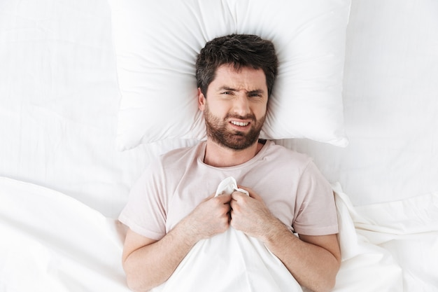 Displeased young man in the morning under blanket in bed