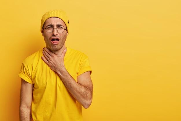 Il giovane scontento soffre di soffocamento, ha sentimenti dolorosi alla gola dopo aver gridato forte