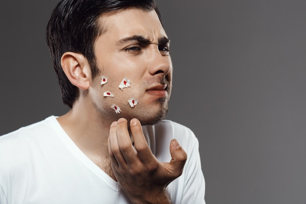Displeased young man touching face after shaving over grey wall