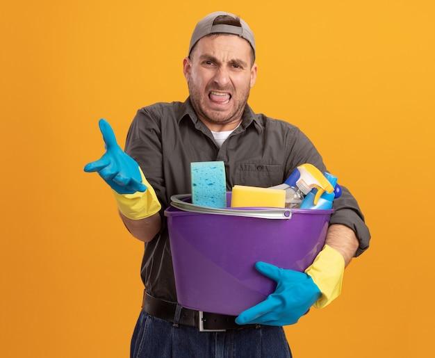 Giovane scontento che indossa abiti casual e berretto in guanti di gomma che tiene secchio con strumenti di pulizia alzando la mano in dispiacere e indignazione in piedi sopra la parete arancione