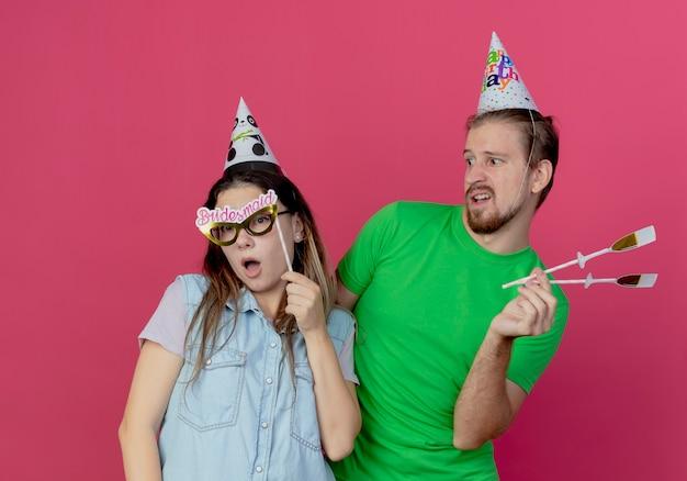 Il giovane dispiaciuto che indossa il cappello del partito tiene i vetri di champagne falsi sul bastone guarda sorpreso la ragazza giovane tiene la maschera per gli occhi sul bastone isolato sul muro rosa