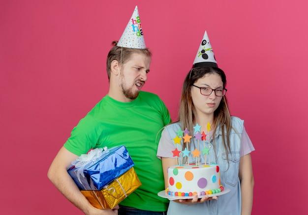 Il giovane dispiaciuto che indossa il cappello del partito tiene le scatole regalo guardando la ragazza infastidita che indossa il cappello del partito e tenendo la torta di compleanno isolata sul muro rosa
