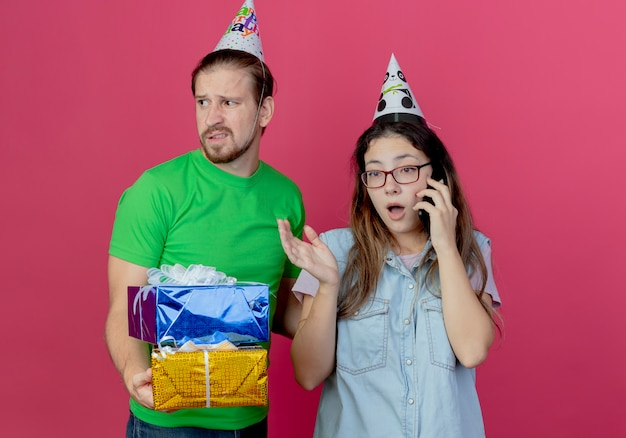 Displeased young man wearing party hat holds gift boxes and looks at side standing with surprised young girl wearing party hat and talking on phone isolated on pink wall