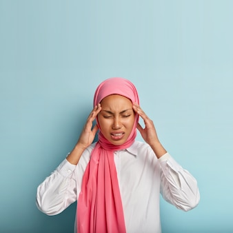 Displeased young muslim woman suffers from painful migraine, touches temples, feels intense, has strong headache, wears pink veil and white shirt