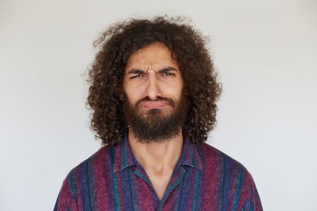 不機嫌な若いかなりひげを生やした男性、口元で見ている巻き毛の黒い髪、折りたたまれた唇で眉をひそめている、縞模様のカジュアルシャツを着