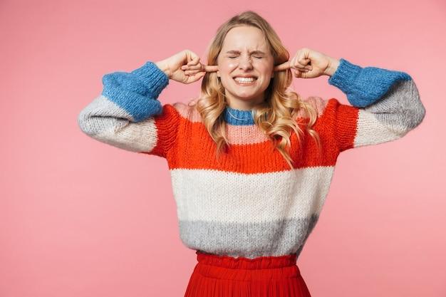 Недовольная молодая довольно красивая женщина позирует изолированной над розовой стеной, покрывающей уши