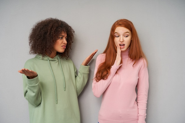 彼女の赤毛のガールフレンドを失望した顔で見て、灰色の壁の上に隔離された感情的に手を上げる不機嫌な若いかなり巻き毛の暗い肌のブルネットの女性
