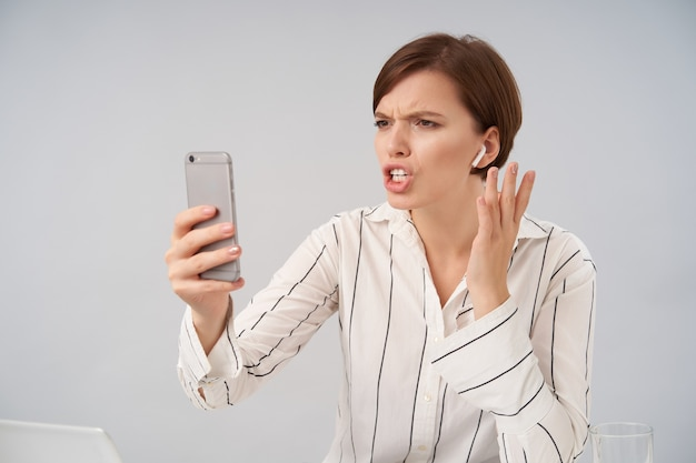 불쾌한 젊은 꽤 짧은 머리 갈색 머리 여성이 그녀의 눈썹을 찌푸리고 스트레스가 많은 전화 대화를하면서 화면을보고 흰색에 포즈