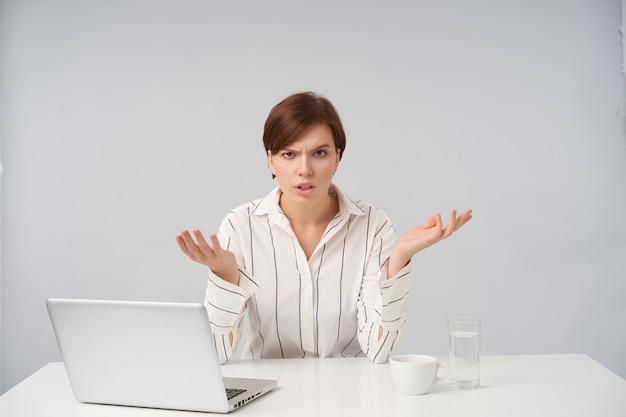 Giovane donna dai capelli corti e dispiaciuta che alza perplesso i palmi delle mani e le sopracciglia accigliate mentre guarda confusamente, posa su bianco
