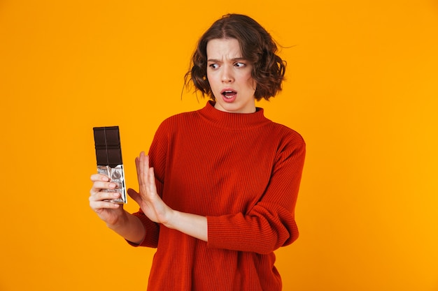 Displeased young pretty woman posing isolated on yellow wall holding chocolate.