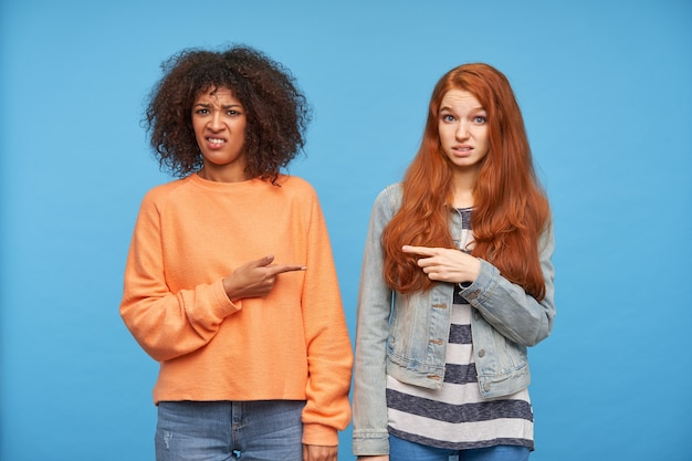 カジュアルな服装で青い壁にポーズをとって、ふくれっ面で見ながら人差し指を上げたままにしておく不機嫌な若いきれいな女性