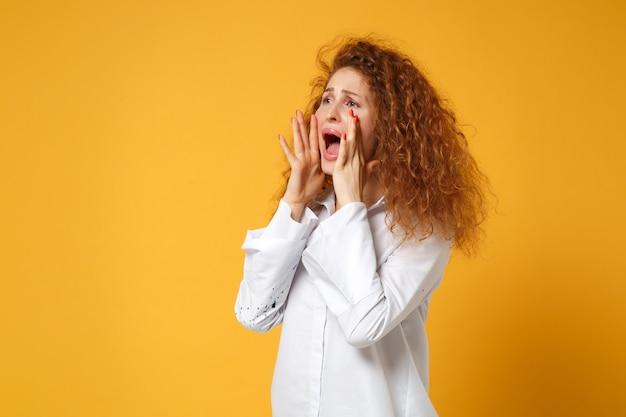 Недовольная рыжая девушка в белой рубашке позирует изолированной на желто-оранжевой стене