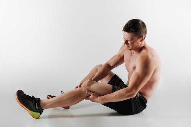 不機嫌な若いスポーツマンは、足に痛みを感じます。