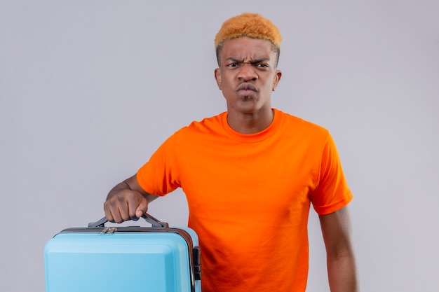 Displeased young traveler boy wearing orange t-shirt holding suitcase with frowning face standing over white wall