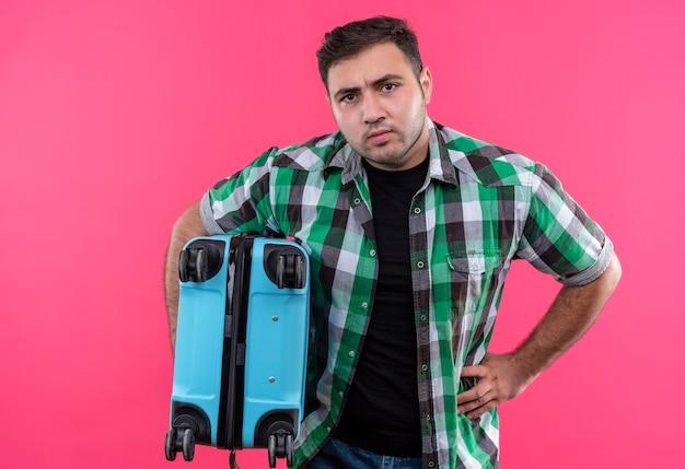 Недовольный молодой путешественник в клетчатой рубашке держит чемодан с сердитым лицом, стоящим над розовой стеной