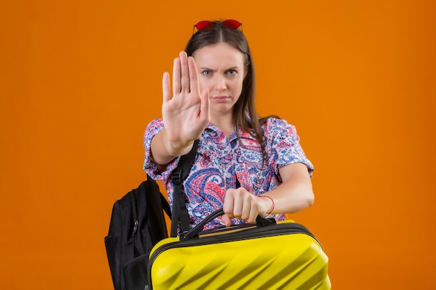 Недовольная молодая путешественница в красных солнцезащитных очках на голове, стоя с рюкзаком, держащим чемодан с открытой рукой, делает знак остановки с сердитым жестом защиты