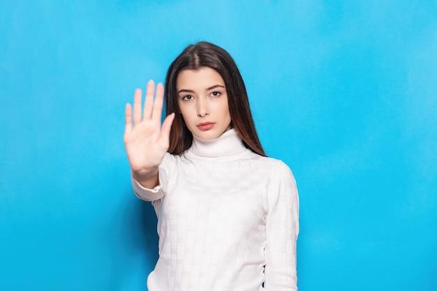 파란색 청록색 배경 스튜디오 초상화에 격리된 캐주얼 흰색 포즈를 취한 불쾌한 젊은 여성 소녀. 사람들이 감정 라이프 스타일 개념입니다. 복사 공간을 비웃습니다. 손바닥으로 중지 제스처 표시