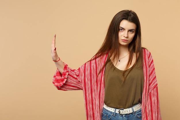 パステルベージュの壁の背景に分離された手のひらを脇に置いて停止ジェスチャーを示す、カメラを探しているカジュアルな服を着て不機嫌な若い女性。人々の誠実な感情、ライフスタイルのコンセプト。コピースペースをモックアップします。