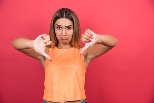 Giovane donna scontenta che fa i pollici verso il basso.
