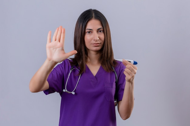 Displeased young woman nurse wearing uniform and with stethoscope holding thermometer standing with open hand making stop gesture