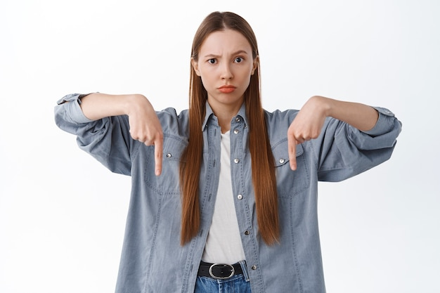 Displeased young woman pointing fingers down with disappointed scolding face, asking for explanation, confused with something strange bellow, standing over white wall