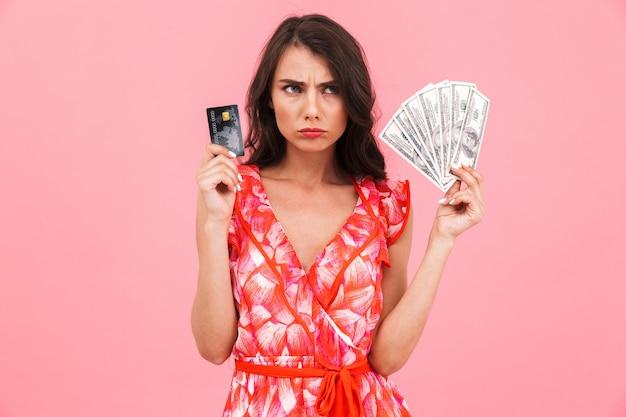 お金とクレジットカードを保持している孤立した壁をポーズする不機嫌な若い女性。