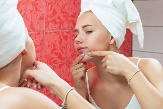 鏡の前でにきびを絞る不機嫌な若い女性