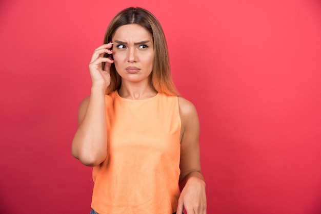 Displeased young woman talking with telephone on red wall.
