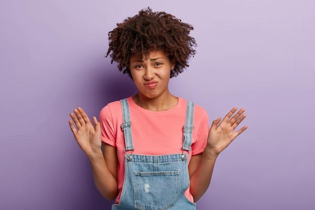 Giovane donna scontenta con un afro che posa in tuta