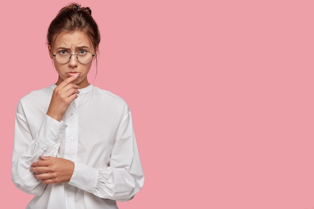 분홍색 벽에 포즈를 취하는 안경으로 불쾌한 젊은 여자