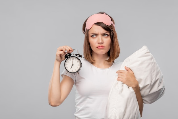 Displeased young woman with pillow holding alarm clock showing 7 am while posing in isolation