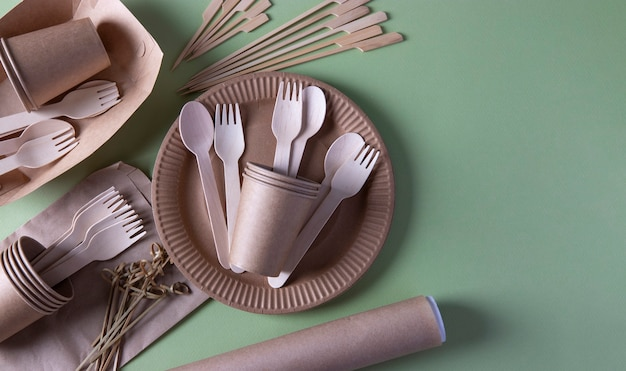 Disposable biodegradable tableware on craft paper plates - forks, spoons, glasses, parchment, wooden and bamboo skewers. zero waste. space for text
