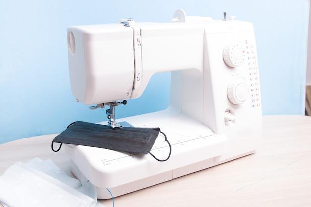재봉틀에 일회용 검은 색 안면 보호대와 수제다면 마스크가 놓여 있습니다.