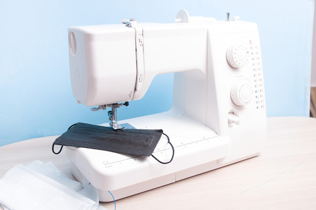 Disposable black face shield and homemade multi-face mask lie on the sewing machine